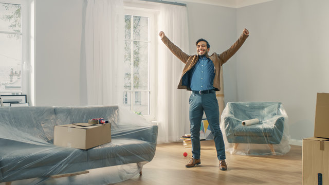 Shot of a Very Happy Man Moves Into His New Apartment and Poses Excited with Raised Arms. Guy Purchased New Home Ready to Start Unpacking Cardboard Boxes.