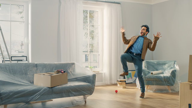Very Happy Man Moves Into His New Apartment, Dances Excited. Guy Purchased New Home Ready to Start Unpacking Cardboard Boxes.