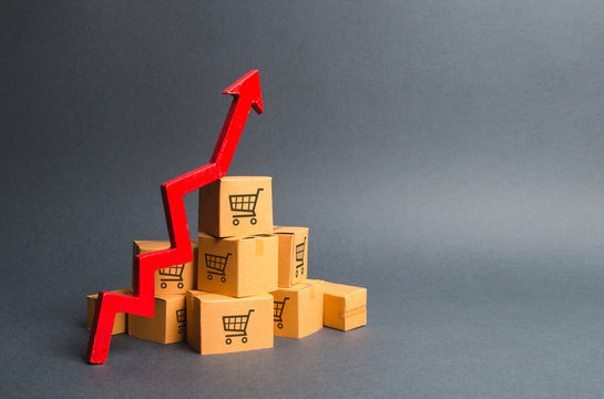 A pile of cardboard boxes with drawing of shopping carts and a red up arrow. The growth rate of production of goods and products, increasing economic indicators. Increasing consumer demand, exports