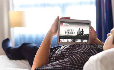 Movie, video and online streaming service in tablet. Man choosing and watching digital film with smart device. Person relaxing. Tv network internet site on screen. On demand video (VOD) concept. Wall mural