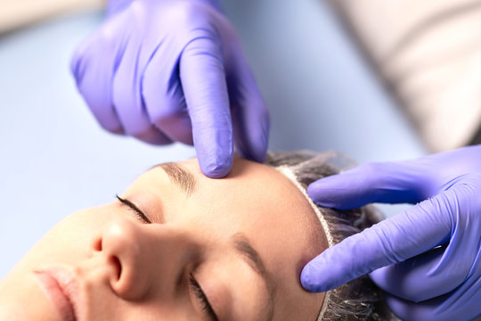 Cosmetologist, plastic surgeon or doctor with patient or customer. Consultation and plan before facial surgery in hospital, skin treatment or facelift in clinic. Professional skincare in beauty salon.