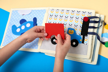 CHILDREN'S LEARNING DEVELOPING BOOK, SEWING FROM A FABRIC. BOY HANDS GATHERING A CAR.