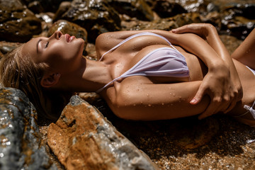 Close up photo of a Pretty young slim blonde woman with big breast wearing white bikini relaxing on the beach lying on the big stones. Leisure summer collection fashion concept