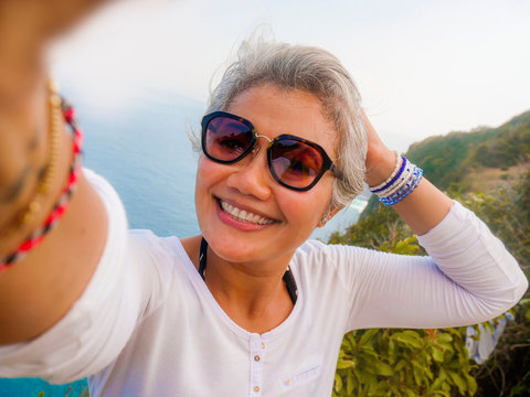 middle age 50s happy and cheerful Asian woman with grey hair taking selfie with mobile phone at beautiful tropical beach island smiling at cliff viewpoint enjoying Summer
