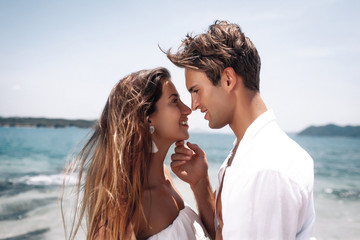 Close up of a beautiful happy couple in love hugging and kissing while standing on a beach