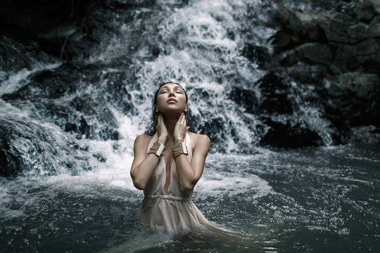 Close up photo of Young beautiful woman with nude back in white dress is standing in the water on a big waterfall.