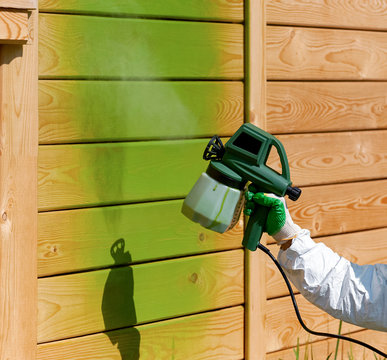 painting wooden wall in green with airbrush process in  open air