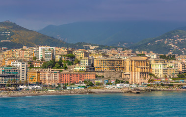 View of Genoa (Genova) from the port when arriving by ship, at sunrise with its yachts and vessels along the water.