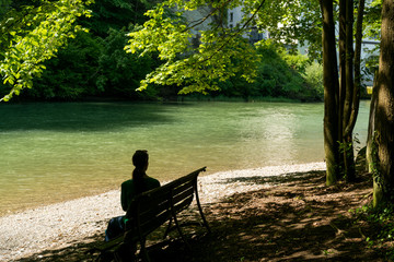 Wall Mural - woman enjoys sitting on a bench under shady trees on an idyllic river bank