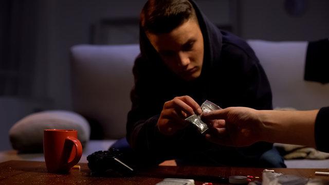 Dealer giving marijuana package to male teenager, drug addiction problem