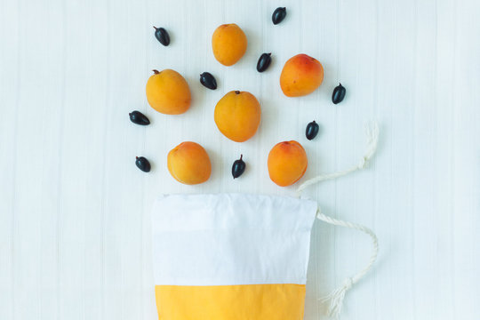 Top view of yellow cotton shopping bag with organic eco apricot fruits on white linen background.