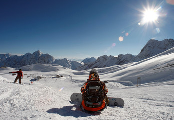 Snowboarder rests watching the Alps scenery during the 2007/2008 winter season opening day at Germany's highest mountain Zugspitze