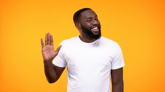 Affable young black man showing palm, waving hand neighborly yellow background