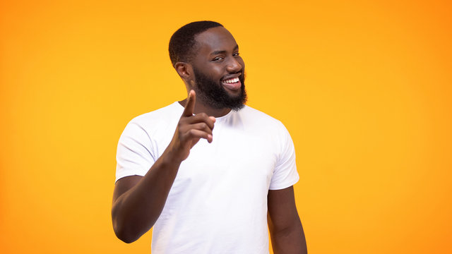 Smug afro-american man pointing finger camera and smiling yellow background