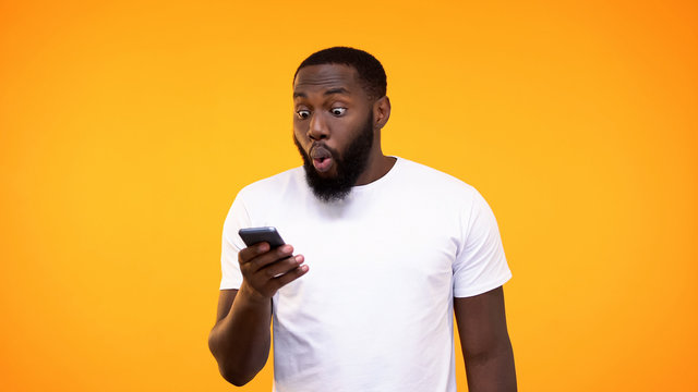 Surprised afro-american guy looking at phone screen, lottery winner, betting app