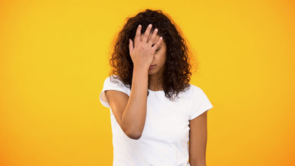 Discontent biracial lady gesturing face palm on camera against yellow background Wall mural