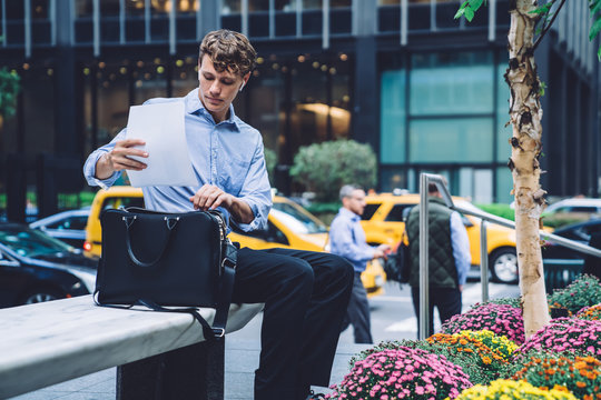 Clever male corporate economist putting paper financial report in leather briefcase while sitting at urban setting in downtown and waiting business partner for discussing accounting outdoors