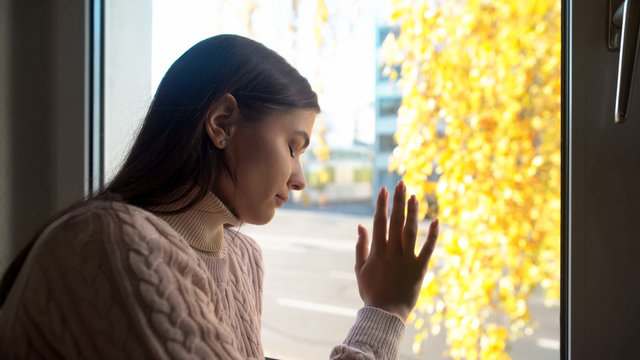 Crying woman touching window, felling sorrow and frustration, autumn depression