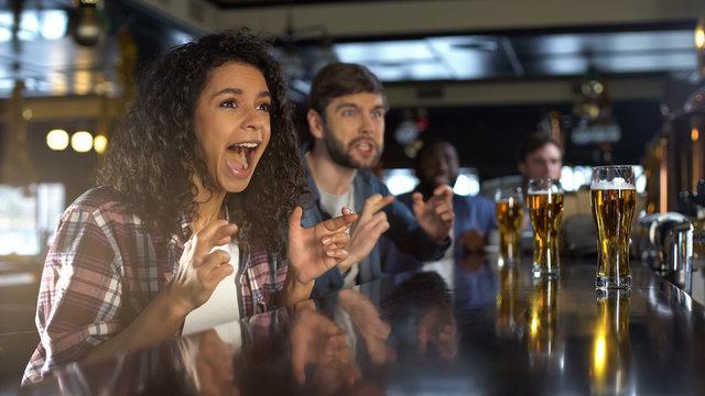 Beautiful biracial lady celebrating favorite team winning game, relaxing in pub