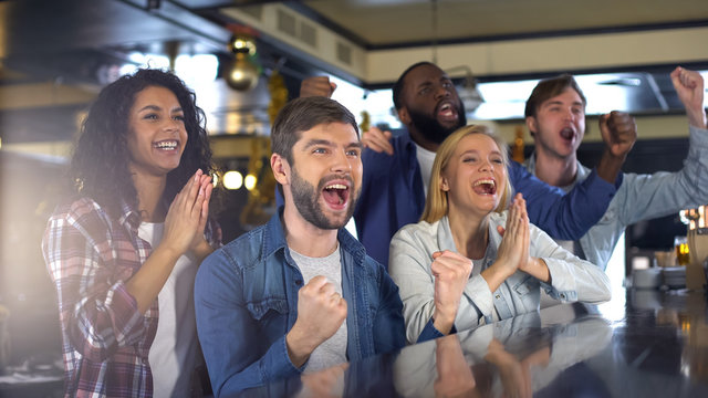 Group of sport fans watching game in bar, rejoicing victory of favorite team