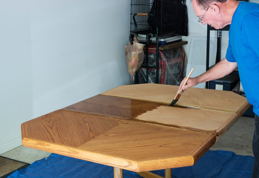 Man Staining A Tabletop
