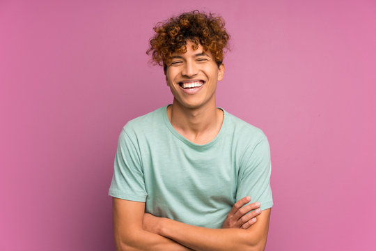 Young african american man over isolated purple wall laughing