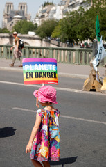 """A child holds a placard which reads """"Planet in danger"""" during a demonstration with youth and environmental activists to urge world leaders to act against climate change, in Paris"""