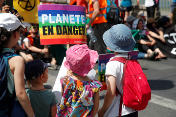 """Children hold a placard which reads """"Planet in danger"""" during a demonstration with youth and environmental activists to urge world leaders to act against climate change, in Paris"""