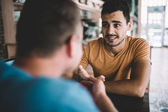 Serious male colleagues discussing information for startup project sitting at cafeteria table and feeling confused on fresh ideas, Caucasian men brainstorming togetherness in coworking space