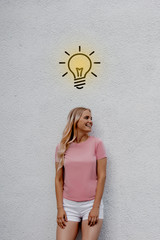 Oh yeah! New great creative idea! Pretty cute, clever smart woman over street wall white background. Light lamp over her head, imagination, brainstorm concept. Elegant fashionable girl. Positive
