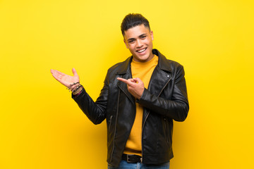 Young man over isolated yellow background holding copyspace imaginary on the palm to insert an ad