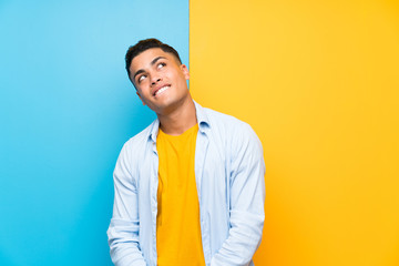 Young man over isolated colorful background laughing and looking up