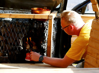 Inventor and owner Maesalu lights a stove in his old yellow Audi car converted into a small sauna in Tallinn
