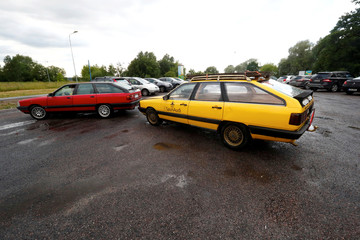 An old yellow Audi car converted into a small sauna is towed to the parking place in Tallinn