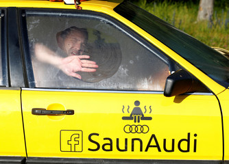Liiv cleans a window as he enjoys bathing in an old yellow Audi car converted into a small sauna in Tallinn