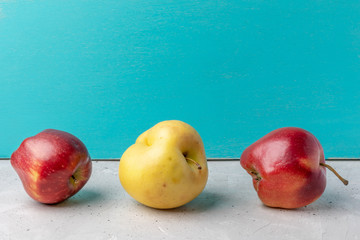 Three ugly apples on concrete table on turquoise background.