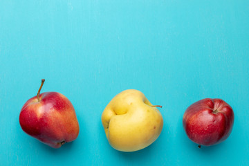 Three ugly apples are lying in line in bottom on turquoise painted wooden  background.