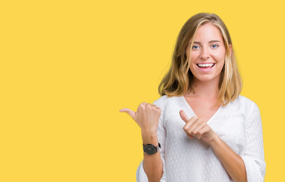 Beautiful young elegant woman over isolated background Pointing to the back behind with hand and thumbs up, smiling confident