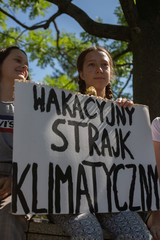 Inga Zasowska holds a placard reading 'Summer Climate Strike' in front of the Polish Parliament building in Warsaw