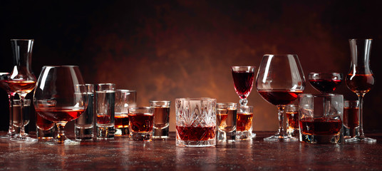 Foto auf AluDibond Bar Set of strong alcoholic beverages in glasses on a brown background.