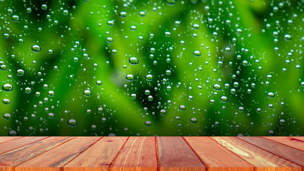 Wood plank with abstract water drop on glass background of glass window shop on a rainy day. Free place for creativity. Background.
