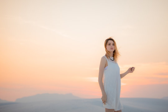 A woman at sunset in the desert sand dunes.