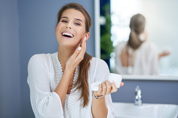 Beautiful brunette woman applying face cream in the bathroom