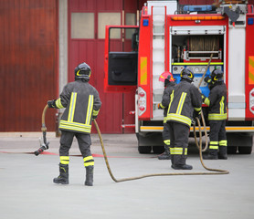 three firefighters in action and the fire engine with hose