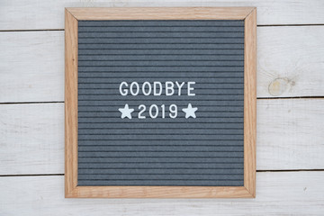 English text goodbye 2019 and two stars on a felt Board in a wooden frame