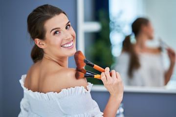 Beautiful brunette woman applying mae up in the bathroom