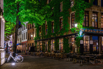 Old cozy narrow street with tables of restaurant in historic city center of Antwerpen (Antwerp), Belgium. Night cityscape of Antwerp. Architecture and landmark of Antwerpen
