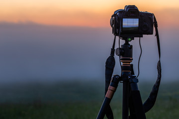 black digital camera on tripod shooting foggy morning landscape at summer with selective focus