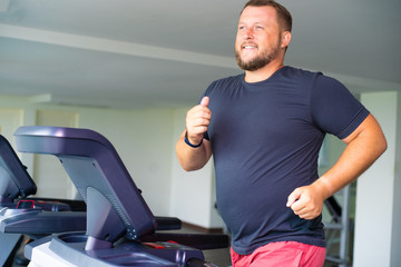 smiling full male runs on a treadmill in a gym. concept of weight loss and sport. side view.