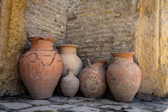 Ancient clay jars against a brick wall